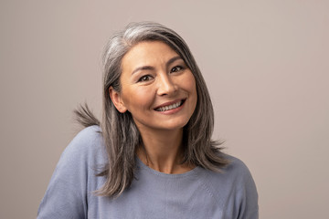 Charming Asian mature woman smiles at camera