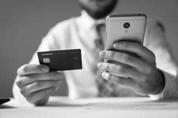 Payment of goods online. Young businessman with a bank credit card in his hands. Online payments through the phone. Online trading on the currency exchange. Smartphone and Internet Commerce.