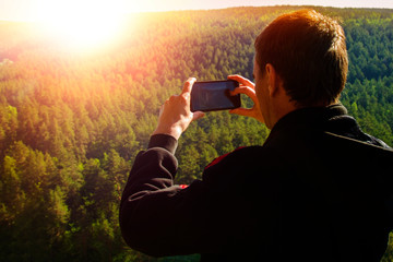 A man takes pictures on the phone natural landscape. nature, travel, tourism, recreation.