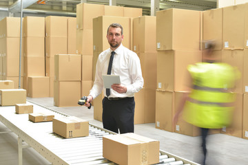 Geschäftsmann im Warenlager Portrait // Workerand Manager in a warehouse in the logistics sector - transport and processing of orders in trade