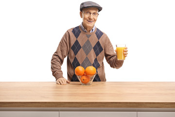 Senior man holding a glass of orange juice behind a wooden counter