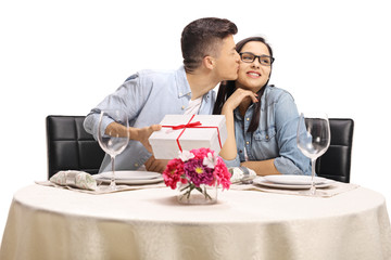 Young guy sitting at a restaurant table, kissing a girl and holding a present