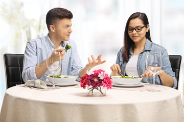 Young male and female eating at a restaurant and talking