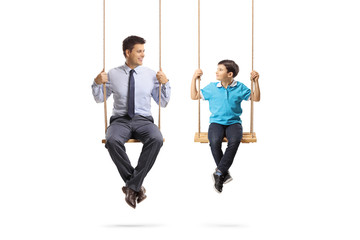 Father and son sitting on swings and looking at eachother