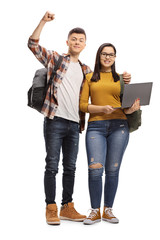 Happy male student embracing a female student standing and holding a laptop computer