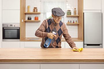 Elderly man cleaning a wooden counter in a kitchen