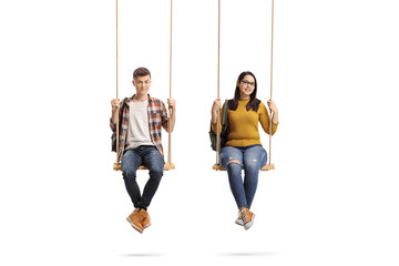 Male and female teenage students sitting on a swing