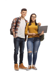 Male and female student standing and holding a laptop computer