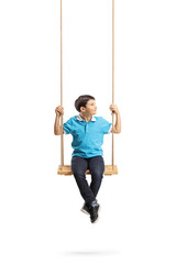 Little boy sitting on a swing and looking to the side