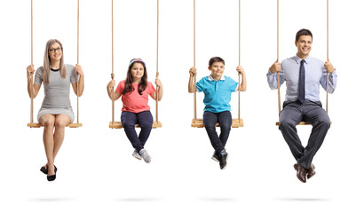 Mother, father, daughter and son sitting on swings and smiling at the camera