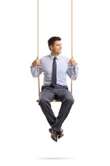 Young professional man sitting on a swing and looking away