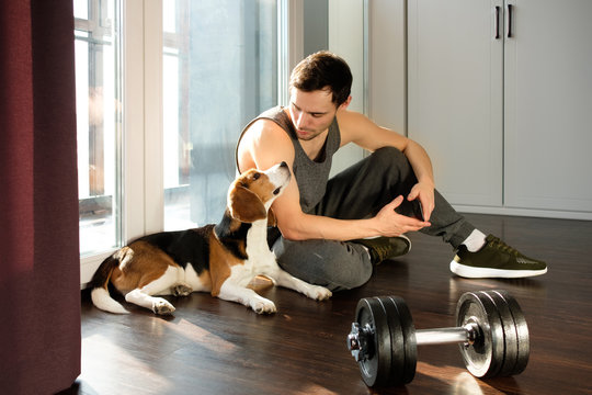 The guy goes in for sports at home with a dog. Exercises for a healthy lifestyle.