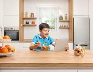 Little boy eating cereals for brekfast at a wooden counter and watching a tablet in a kitchen