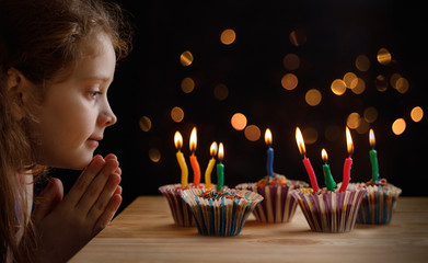 Obraz Cute little girl with party hat looking an the candles on birthday cakes. - fototapety do salonu