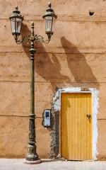 Yellow door and street lamp in Marrakech, Morocco