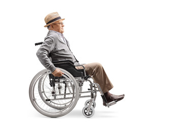 Elderly man in a wheelchair pushing himself manually