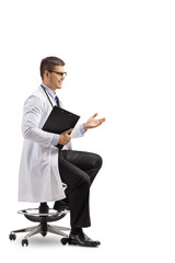 Young male doctor sitting and gesturing a conversation