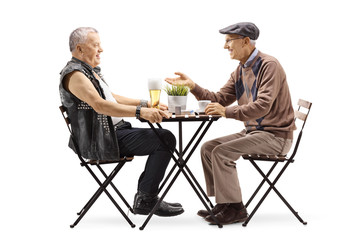 Mature punker drinking beer at a table and talking with an elderly man drinking coffee