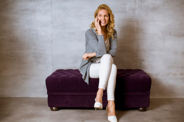 Blonde woman sitting on a purple sofa and using a mobile phone