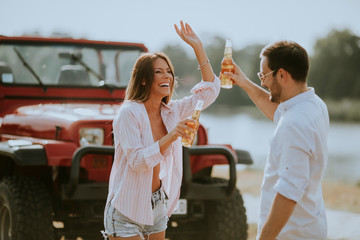 Young woman and man having fun outdoor near red car