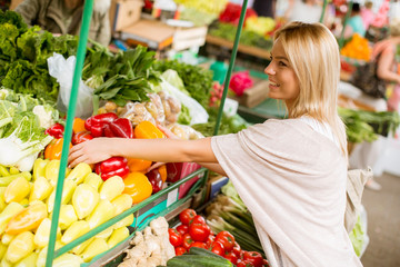 Cute young woman buying vegetables at the market