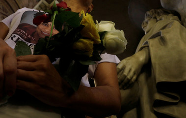 A woman, wearing a T-shirt with a picture of Marielle Franco, holds flowers during a mass marking the first anniversary of the murder of late activist and councilwoman Marielle Franco, in Rio de Janeiro