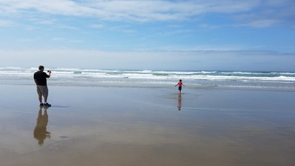 father taking picture of son in sand and water at beach