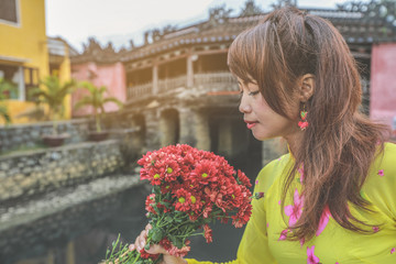 Selective focus on red flowers, beautiful women in Ao Dai Vietnam traditional dress hoilding a branch of red flowers