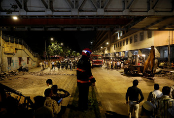 Rescue members stand at the site of a footbridge collapse outside the Chhatrapati Shivaji Terminus railway station in Mumbai