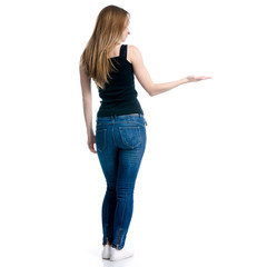 Woman in jeans standing showing pointing on white background isolation, back view