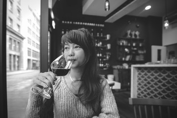 Beautiful asian woman drinking wine in black and white. Red wine concept