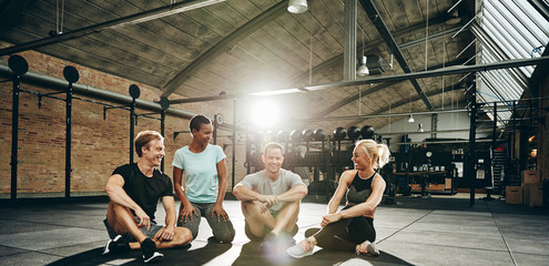 Smiling friends sitting and talking together after a gym workout