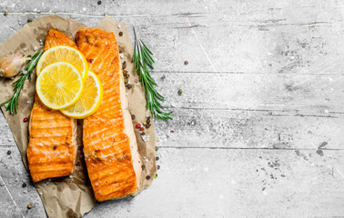 Grilled salmon fillet with slices of fresh lemon.