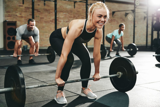Smiling young woman lifting heavy weights at the gym
