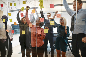Cheering businesspeople celebrating during an office brainstormi