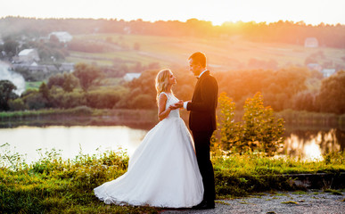 Lovely couple reach out their hands while standing in the rays sunny Fototapete
