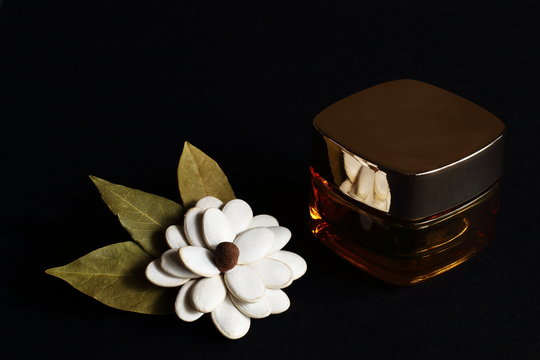 Decorative homemade flower from white pumpkin seeds, decorated with black peppercorns and bay leaves and face cream on black background. Play of light and shadow. Concept — beauty, gift.