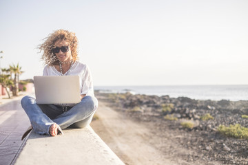 Technology and travel. Working outdoors. Freelance concept. Pretty young woman using laptop  beach.