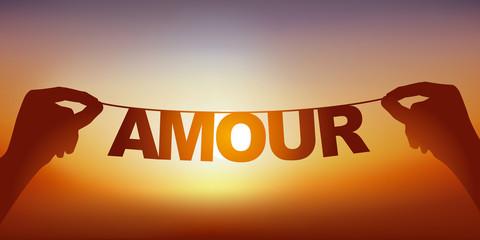 Concept du bonheur d'être amoureux, avec deux mains qui tiennent une guirlande sur laquelle est écrit le mot amour devant un ciel ensoleillé.