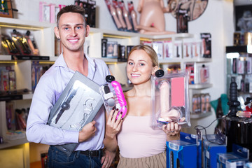 adult couple buying sex toys in shop.