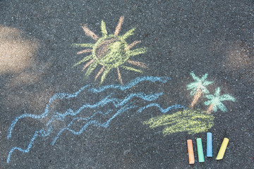 Closeup top view of child's chalk drawing of tropical beach. Blue sea water, yellow sun, sandy island with green palms growing painted at sidewalk outdoors at city park. Horizontal color photo.