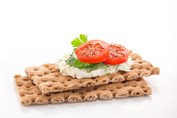 Crispbread with soft cottage cheese and red tomatoes and green cucmber slices