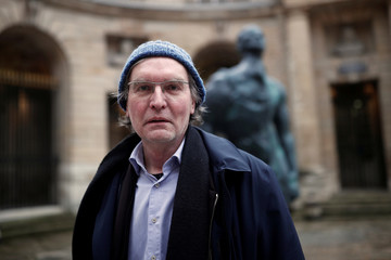 """German artist Thomas Schutte stands in front of his artwork """"Man in the Wind"""" during a press visit of a retrospective of his work at the Monnaie de Paris in Paris"""
