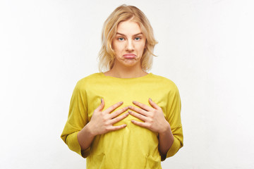 Breast augmentation concept, small size. Upset young woman with a displeased facial expression touches her tiny tits in the studio on a white background