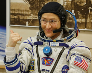 The International Space Station (ISS) crew member Christina Koch of the U.S. gestures after donning space suits shortly before their launch at the Baikonur Cosmodrome