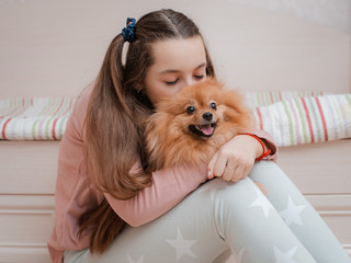 Teenage girl with a dog breed Spitz rejoices with a pet at home on the floor.