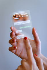Woman hand holding transparent futuristic smartphone with Messaging app on screen. Social media, business, technology and people concept