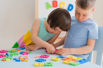 A boy and a girl collect a soft puzzle at the table. Brother and sister have fun playing together in the room.