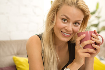 Gorgeous young woman smiling seductively to the camera holding a cup of coffee relaxing at the local cafe copyspace playful flirt flirtatious romantic girl feminine sensuality positivity lifestyle stu