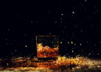 Isolated shot of whiskey with splash on wooden background